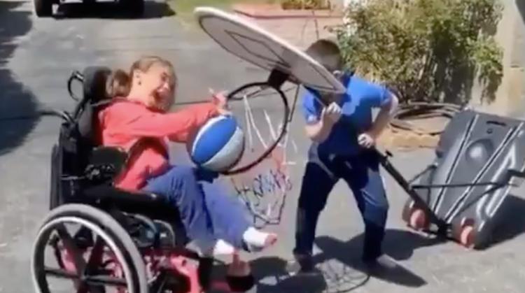 Jongetje helpt zusje in rolstoel met scoren afbeelding nieuwsbericht